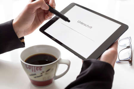 Hands with tablet and coffee signing Stock Photo - 26747286