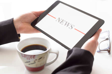 Hands with tablet and coffee reading news photo