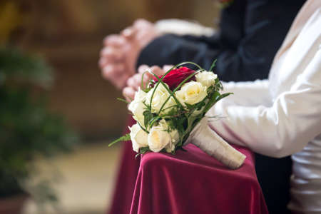 Bridal bouquet in front of bride and groom in church