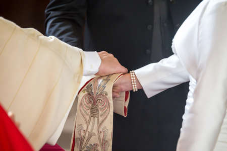 Priest giving blessing to a couple at a wedding ceremony in a church