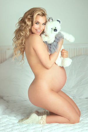 Beautiful young blonde pregnant woman naked, looking at camera. Smiling happy girl. Stock Photo
