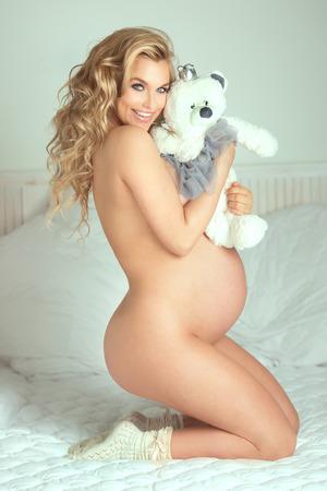 donna completamente nuda: Bella bionda giovane donna incinta nuda, guardando a porte chiuse. Sorridente ragazza felice.