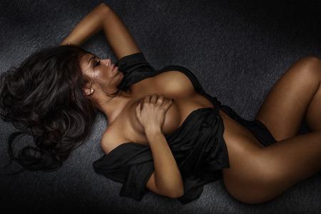 nude young: Чувственный молодая женщина позирует голой, лежа. Длинные вьющиеся волосы. Гламур макияж. Сексуальный стиль.