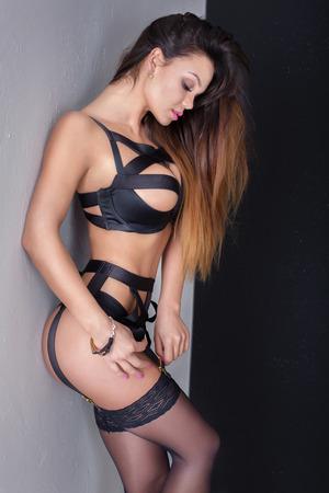 pechos: mujer morena atractiva que presenta en ropa interior erótica. cuerpo delgado perfecto. Maquillaje del encanto.