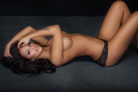 Naked beautiful woman lying on the floor. Beautiful brunette lady.