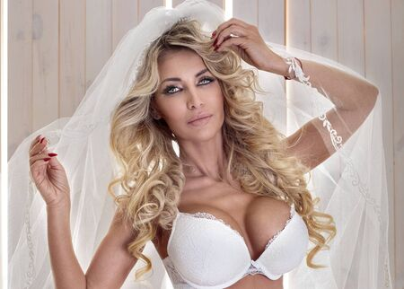 elegance fashion girls look sensuality young: Sensual blonde bride posing in white lingerie and veil. Stock Photo