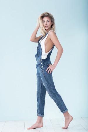 Niña caucásica rubia posando en jeans sobre fondo azul pastel.