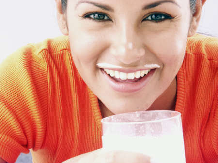 white moustache: Young hispanic female drinking a glass of milk
