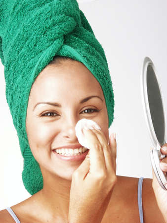 powder puff: Beautiful young latin woman holding a powder puff and a mirror on white background