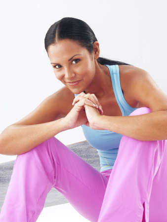 Young woman in gym attire on white background photo