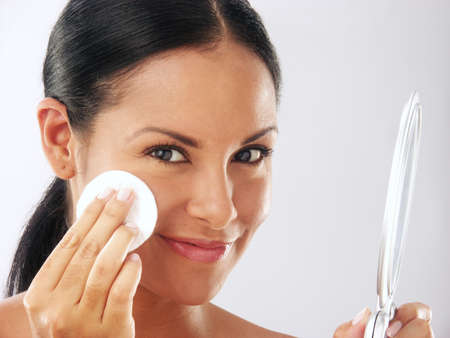 Beautiful young latin woman holding a powder puff and a mirror on white background