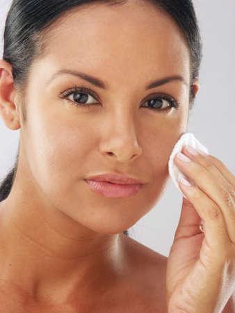 powder puff: Young latin woman using a powder puff