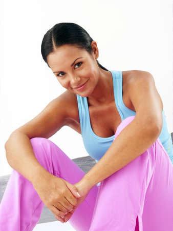 Young woman in gym attire on white background