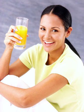 nutritive: Young hispanic female drinking a glass of juice Stock Photo