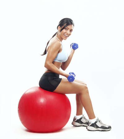 Young woman doing fitness exercise with a red ball