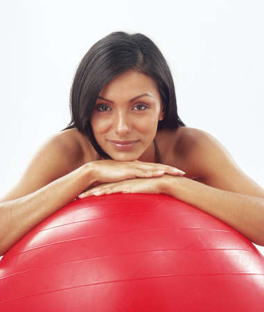 Young woman doing fitness exercise with a red ball photo