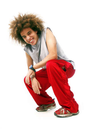 squatting down: Young man with afro hairstyle squatting down on white background