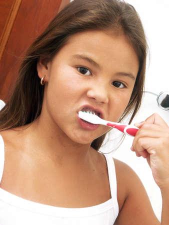 Little hispanic girl brushing her teeth photo