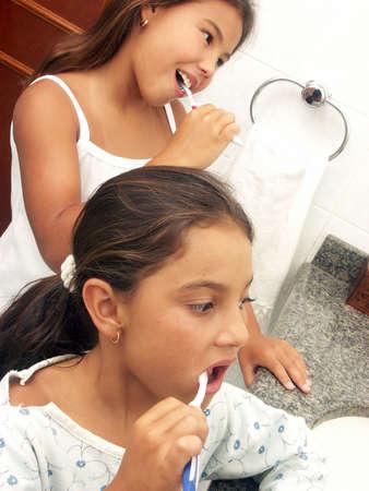 Two hispanic girls brushing their teeth photo