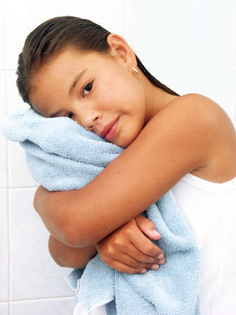 rejuvenated: Little hispanic girl hugging a blue towel