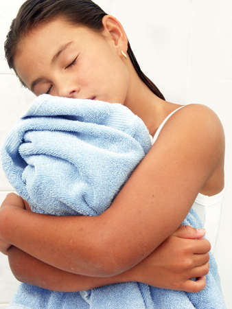 Little hispanic girl hugging a blue towel Stock Photo - 22413336