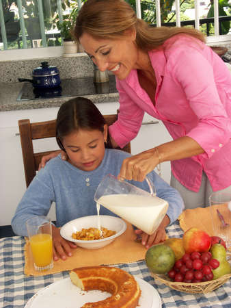 Hispanic woman pouring milk into a bowl of cereal for her daughter Stock Photo - 22442883