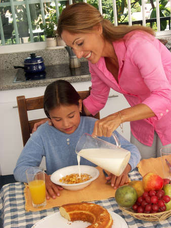 Hispanic woman pouring milk into a bowl of cereal for her daughter Stock Photo - 22442894