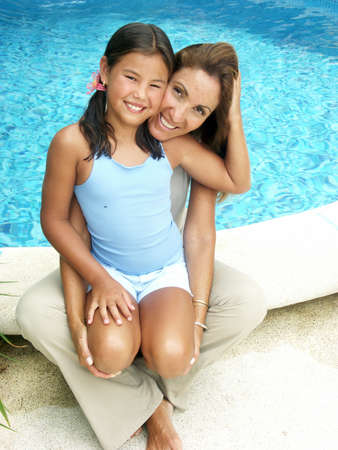 Hispanic mother and daugther sitting beside the swimming pool photo