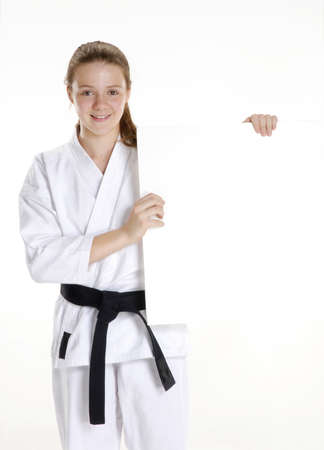 Young caucasian girl in martial arts uniform holding a white board