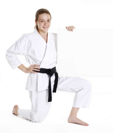 Young caucasian girl in martial arts uniform holding a white board photo