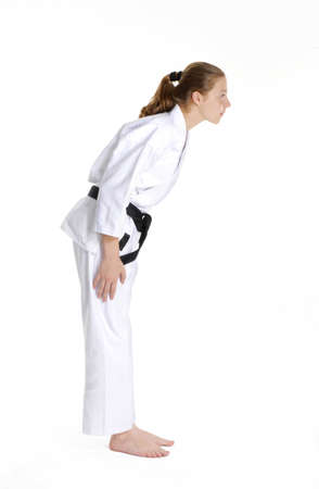 Young caucasian girl in martial arts uniform doing a stunt