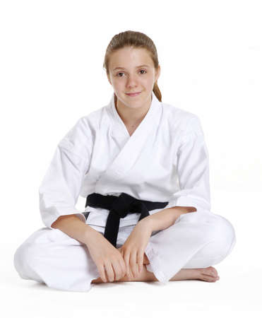 legged: Young caucasian girl in martial arts uniform sitting cross legged