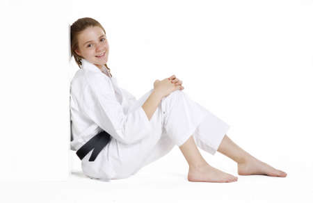 Young caucasian girl in martial arts uniform sitting on the floor photo