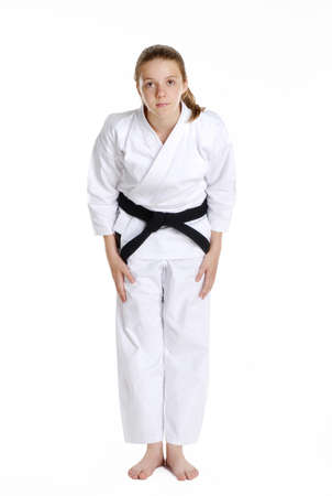 bowing: Young caucasian girl in martial arts uniform bowing Stock Photo