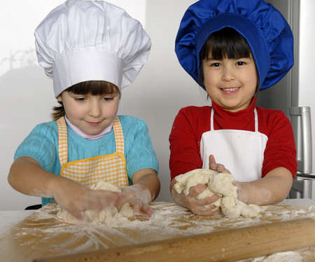 children cooking: Kids with chef hats kneading dough