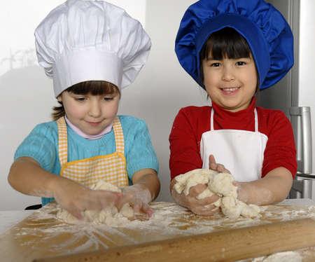 niños cocinando: Niños con sombreros del cocinero que amasan la pasta