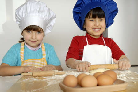 Kids with chef hats using the rolling pin photo
