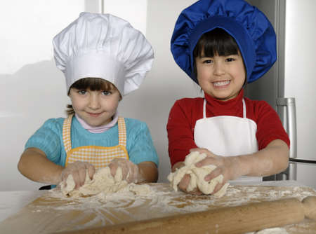 Kids with chef hats kneading dough photo