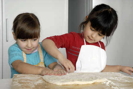 Kids with aprons baking in the kitchen Banque d'images