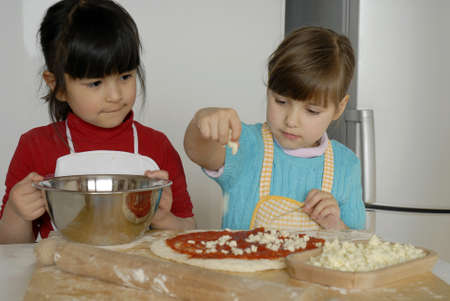 Kids cooking a pizza in the kitchen photo