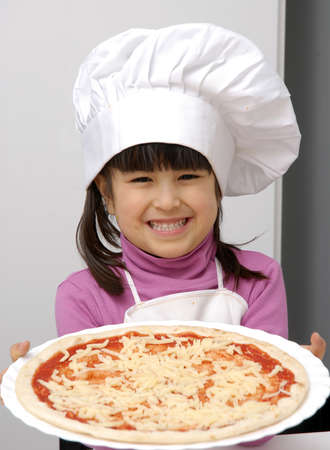 Kid in chef hat and apron holding a pizza Stock Photo