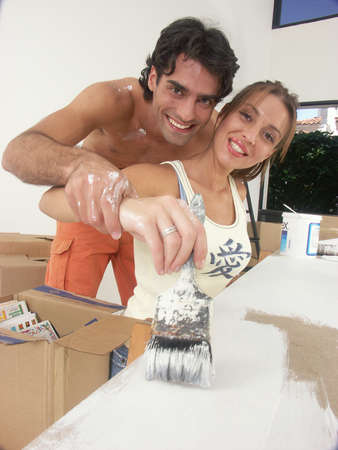 Hispanic couple working on their new home together photo