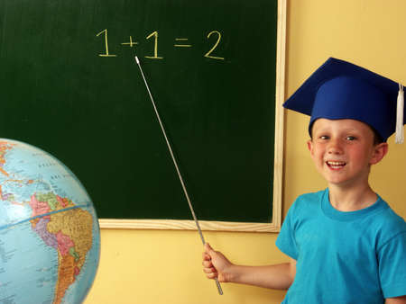 imitating: Little boy with mortar hat teaching in the classroom
