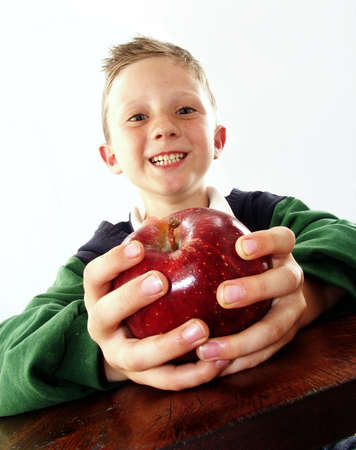 Little boy holding an apple on white background photo