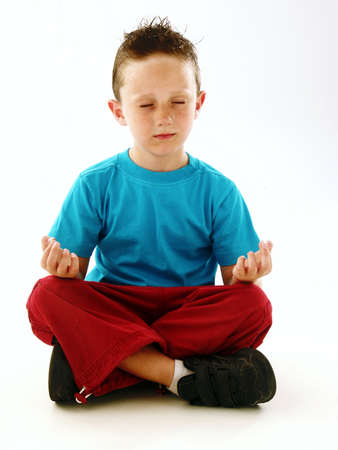 Little boy in a yoga position on white background Stock Photo