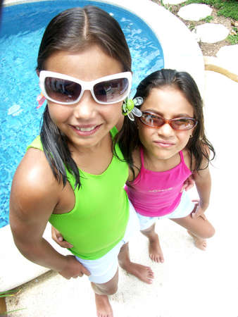 Little hispanic girls wearing sunglasses beside a swimming pool