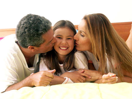 Hispanic parents kissing their daughter photo
