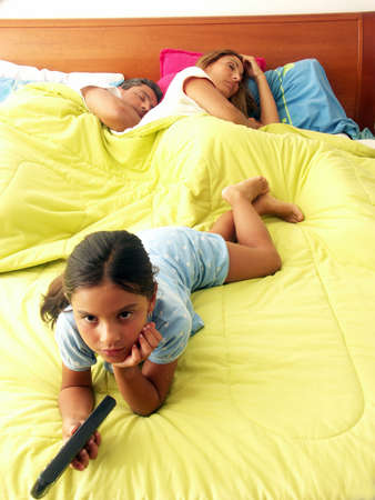 Hispanic girl watching tv while her parents are asleep on bed Stock Photo - 22480449