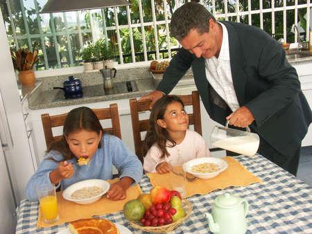 Hispanic man pouring milk for his children in kitchen