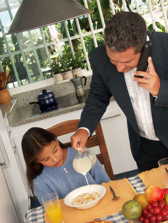 Hispanic man on phone while pouring milk for a child in kitchen photo